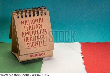 October - National Italian American Heritage Month, handwriting in a desktop calendar against paper abstract in colors of national flag of Italy (green, white and red), reminder of cultural event