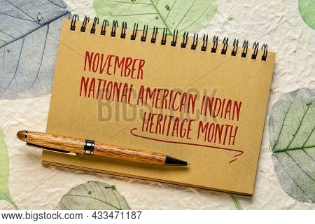 November - National American Indian Heritage Month, handwiting in a spiral notebook against handmade paper with leaf inclusions, reminder of historical and cultural event