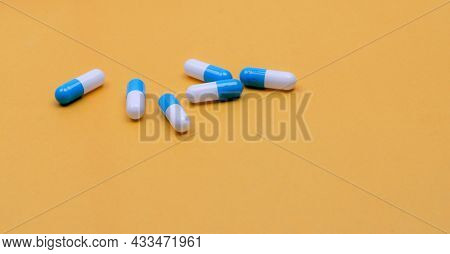 Blue-white Capsules Pill On Yellow Background. Pharmacy Banner. Capsule Pills Manufacturing Industry