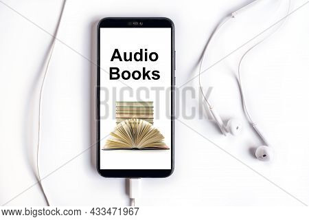 Smartphone With Earphones And Audiobooks Collection On Screen