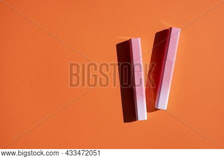 Lip Gloss In A Pink-to-white Gradient Case. Top View On Orange Background. Beauty Concept For Lips.