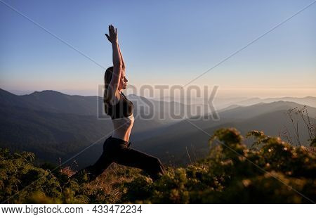 Side View Of Sporty Young Woman Doing Yoga Exercise On Grassy Hill With Blue Morning Sky On Backgrou
