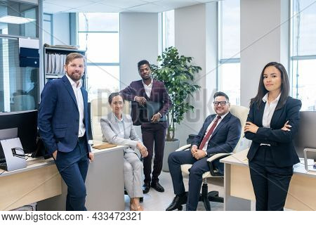 Large group of young successful intercultural white collar workers in open space office