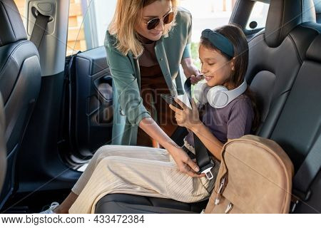 Young female helping her little daughter with smartphone fasten safety belt before driving to school