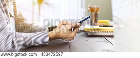 Young Woman Using Mobile Phone While Working At Home With Laptop. Young Freelancer Female Sitting On