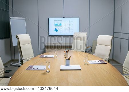Armchairs around large oval wooden table with papers, glasses and pens in boardroom