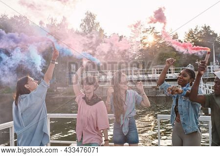 Large group of young multiracial friends with firecrackers dancing on pier on summer weekend