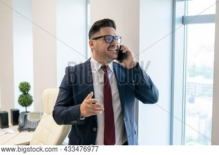 Caucasian white collar worker in formalwear talking on mobile phone in front of camera