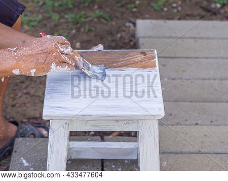 Senior Man Hand Paints With Brush An Old Wooden Chair Without A Backrest. Hand Of Man. Old Chairs Ar