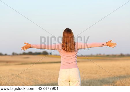Back View Of A Woman Outstretching Arms In Harvested Field