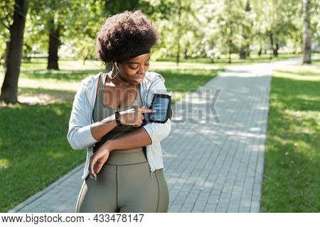 Happy sportswoman pointing at smartphone screen during outdoor training
