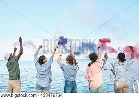 Young ecstatic friends with multi-colored firecrackers dancing in front of waterside on hot summer day