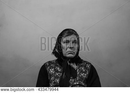 Defocus Portrait Of 60s Russian Grandmother Senior Old Woman Seating Indoors. Old Women In Shawl. Sa