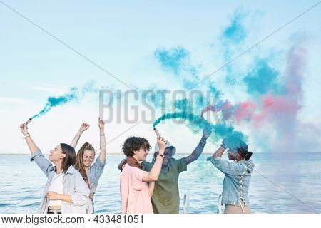 Young joyful friends dancing with firecrackers while enjoying outdoor party