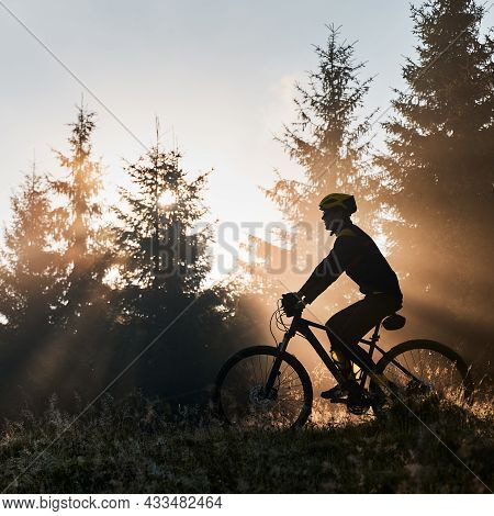 Silhouette Of Young Man In Cycling Suit Riding Bicycle In Forest Illuminated By Morning Sunlight. Bi