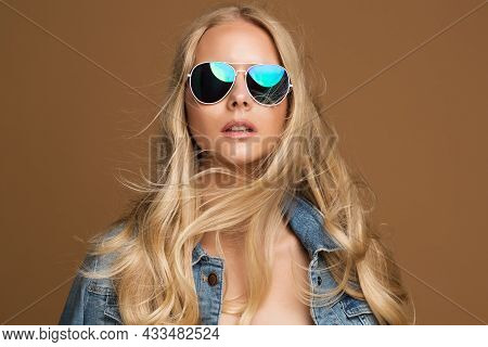 Fashion Blond Model Girl Portrait In Sunglasses. Hipster Style Blond Woman In Denim Jacket Over Beig