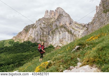 Young Traveler Woman, With A Backpack On Her Back, Ascending A Mountain During An Excursion Through
