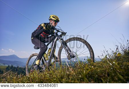 Young Man Cycling Uphill On Sunny Day With Blue Sky On Background. Male Bicyclist In Cycling Suit Cl
