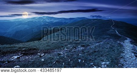 Mountain Landscape At Night In Spring. Path Through Meadow In Grass On The Hill In Full Moon Light.