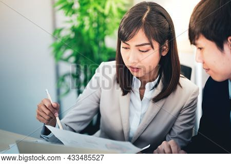 At Work, A Young Asian Woman Holds A Piece Of Paper And Points To It While Talking Or Recommending S