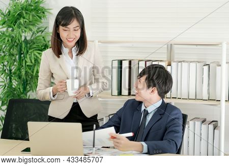 A Group Of Asian Businesspeople Are Enjoying A Casual Conversation. In The Office, Employees Are Sta
