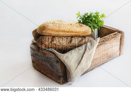 Assortment Of Bread In A Wooden Old Rustic Box. Various Types Of Greens For Bread. Studio Photo. Sti
