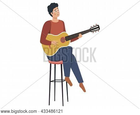 Young Man Playing Guitar At Home Sings Song. Private Guitar Lessons. Guy Sitting On Chair With Music