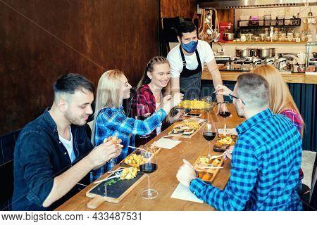 Happy Best Friends Enjoy Time Together At Restaurant While Waiter Wearing Face Mask Serving Food Dur