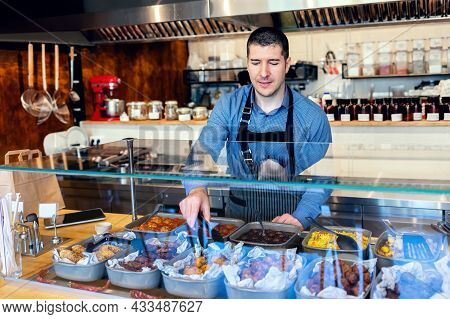 Happy Waiter Wearing Apron Serving Takeaway Food To Customer At Counter In Small Family Restaurant -