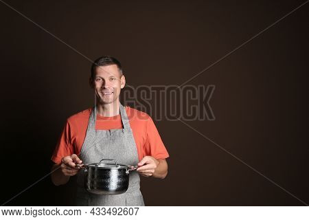 Happy Man With Cooking Pot On Brown Background. Space For Text