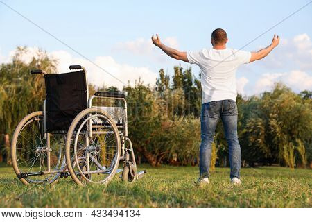 Man Standing Near Wheelchair On Sunny Day, Back View. Healing Miracle
