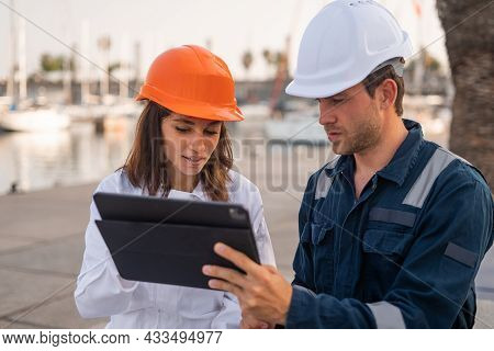Serious Male Engineer And Female Inspector In Hardhats Discussing Information On Tablet During Meeti