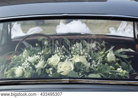 A Chic Bouquet Of White Roses Behind The Glass Of The Back Seat Of A Wedding Car