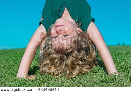 Kid Playing Upside Down In The Meadow. Happy Healthy Caucasian Child Boy With Lying On The Grass Fie