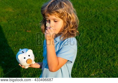Kid Saving Coin Money With Piggy Bank. Cash And Investment. Boy Collecting Money To Money Box Piggyb