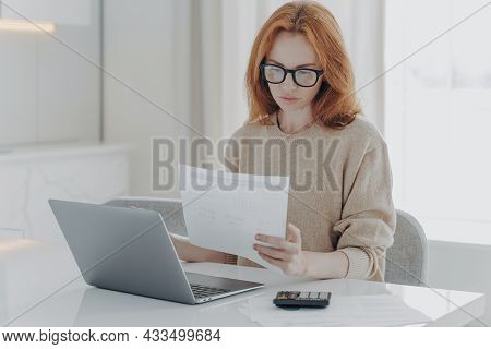 Young Focused Red-haired Woman In Spectacles Calculating Budget At Home, Sitting At Table With Lapto