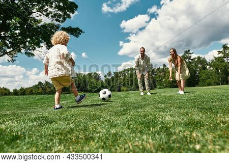 Young Parents Teaching Their Little Son Playing Football On Grass Field In The Park On A Summer Day.