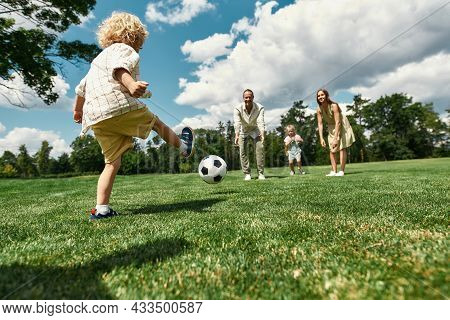 Little Boy Kicking The Ball While Parents And Sister Watching. Young Family Playing Football On The