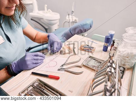 Dentist Cutting Braces Wire While Sitting At The Table With Orthodontic Instruments. Woman Orthodont