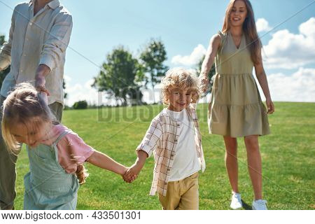 Cute Little Boy Smiling At Camera, Holding Hands Together With His Parents And Sister And Walking On