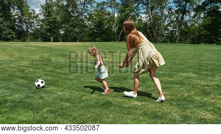 Active Young Mother Playing Football Together With Her Little Daughter On The Grass Field In The Par