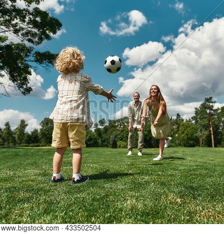 Young Parents Playing Footabll With Their Little Son On Grass Field In The Park On A Summer Day. Chi