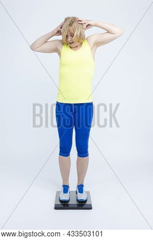Body Weighе Ideas. Mature Caucasian Sportswoman In Jogging Blue And Yellow Outfit While Checking Her