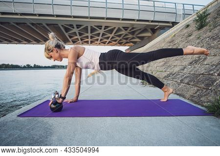 Young Woman Is Exercising Kettlebell Pilates Outdoor.