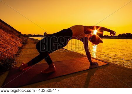 Young Woman Is Exercising Outdoor. She Is Practicing Yoga On Sunny Day. Camatkarasana, Wild Thing Yo