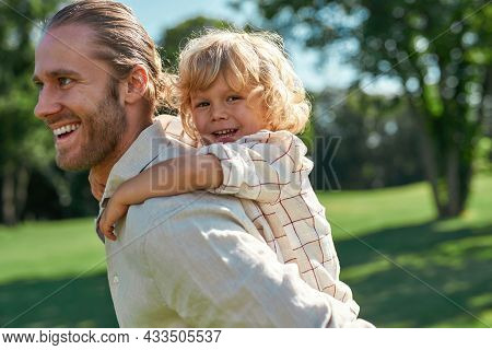 Portrait Of Cheerful Little Boy Playing In The Park With His Father Giving Son Piggyback Ride On His