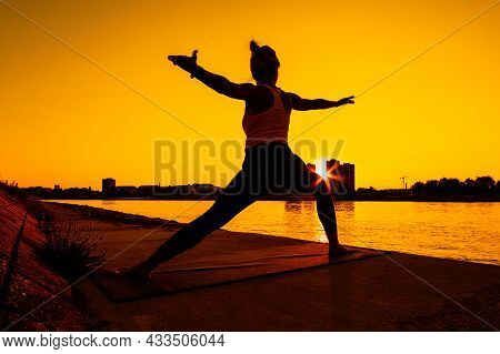 Young Woman Is Exercising Outdoor. She Is Practicing Yoga On Sunny Day. Virabhadrasana / Warrior 2 P