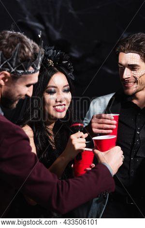 Smiling Asian Woman In Vampire Halloween Costume Singing Karaoke Near Men On Black