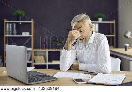 Tired Stressed Man Sitting At Office Desk With Laptop Takes Off Glasses And Rubs Eyes
