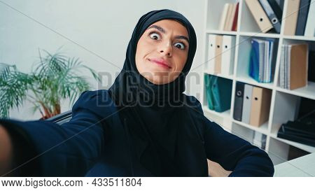 Smiling Young Muslim Businesswoman Grimacing While Taking Selfie